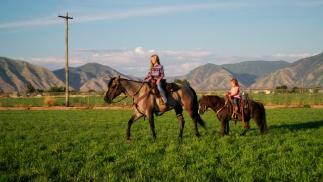 馬を持つ若いカウボーイの子供たち - 乗馬点の映像素材/bロール