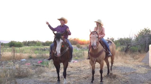 vídeos de stock, filmes e b-roll de jovens vaqueiros a cavalo percorrendo uma fazenda ao pôr do sol - montar um animal