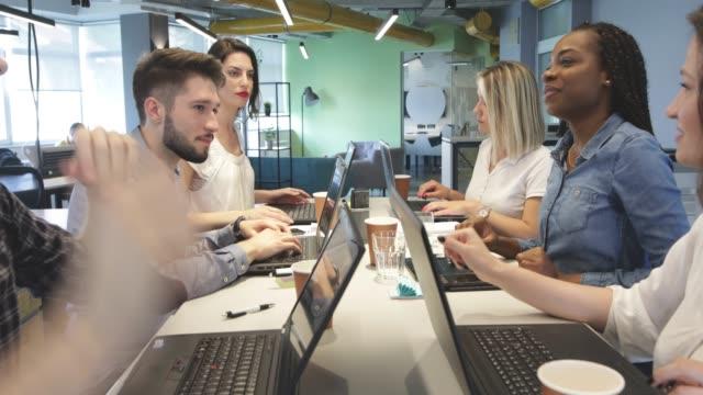 junge kollegen im modernen büro - coworking space stock-videos und b-roll-filmmaterial