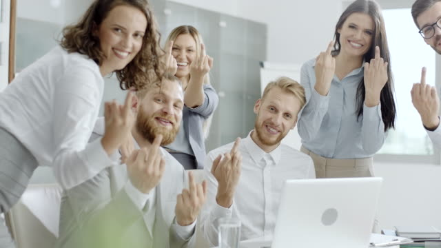 Young coworkers showing middle finger