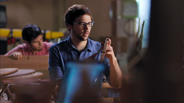 vídeos de stock, filmes e b-roll de young craftsman chisels wood in workshop while artist designs frame on laptop computer - plano de arquitetura