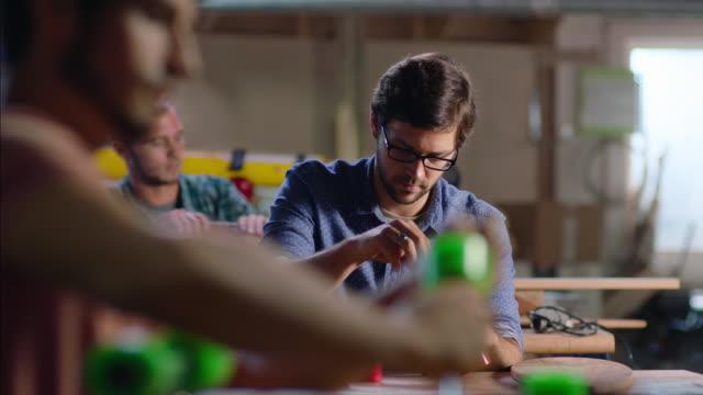 Young craftsmen fasten wheels and assemble skateboard kits in custom skate shop