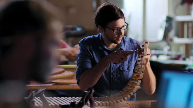 vidéos et rushes de young craftsmen work on various projects in modern wood shop - chaise