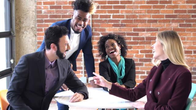 若い創造的なビジネスの人々は、会議、笑い - レンガの壁点の映像素材/bロール