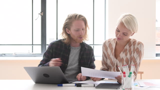 Young creative businessman with lap talking to mid adult woman in office