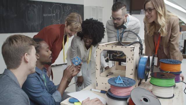vídeos de stock, filmes e b-roll de 4 k: pessoas jovens criativas de trabalhar de impressoras 3d. - digitalização 3d