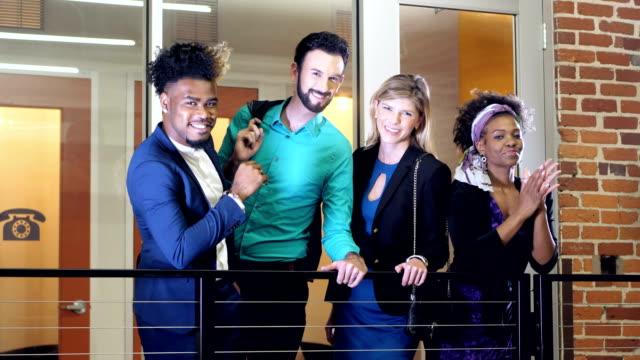 junge kreative stehen im bürokorridor - multi ethnic group stock-videos und b-roll-filmmaterial