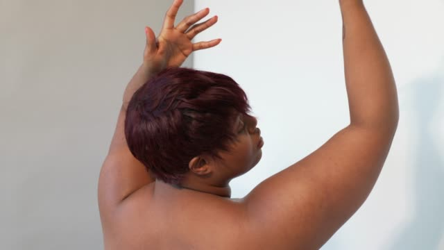 A young curvaceous woman with her hands above her head.