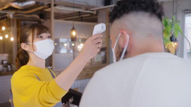 若い顧客は、手の消毒剤を適用し、カフェの入り口で彼の温度をチェックしてもらいます - 温度計点の映像素材/bロール