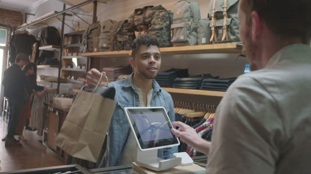 vídeos y material grabado en eventos de stock de young customer completes transaction on tablet and shakes hands with cashier in modern downtown clothing shop. - bolsa de papel