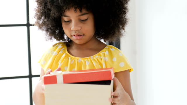 young cute african girl opening a gift box - christmas gift stock videos & royalty-free footage