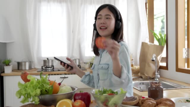 young cute asian woman cooking salad in kitchen room with happyness and listen music with earphone and dancing.