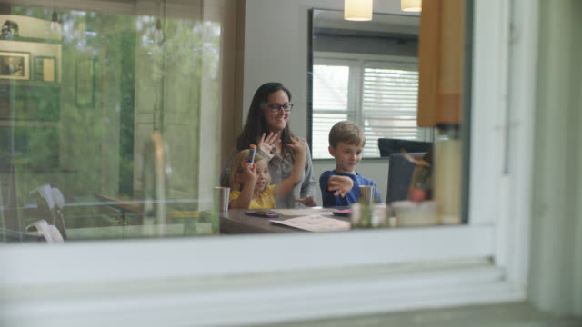 slo mo. young cute family waving goodbye while video conferencing in kitchen. - home interior stock videos & royalty-free footage