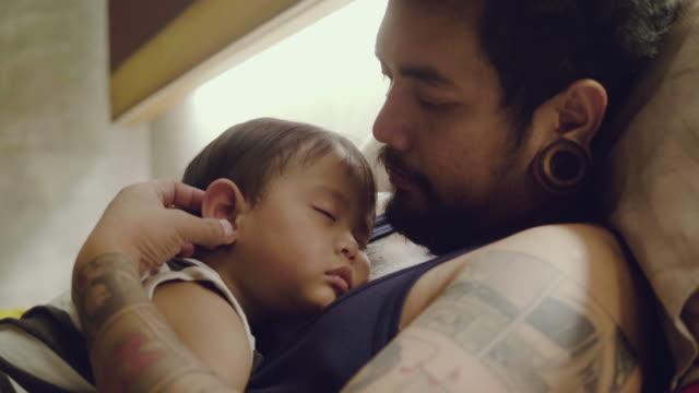 vidéos et rushes de jeune garçon mignon peu dormir avec papa. - tatouage