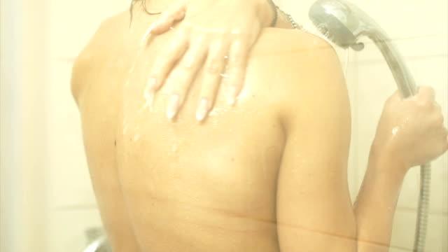 Junge nette Frau eine erfrischende Dusche nehmen