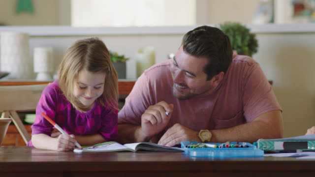 MS. Young dad and daughter laugh and draw funny pictures in notebook with magic markers.