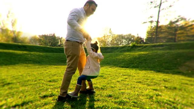 vídeos y material grabado en eventos de stock de papá joven y su hija bailando en el parque público - father day