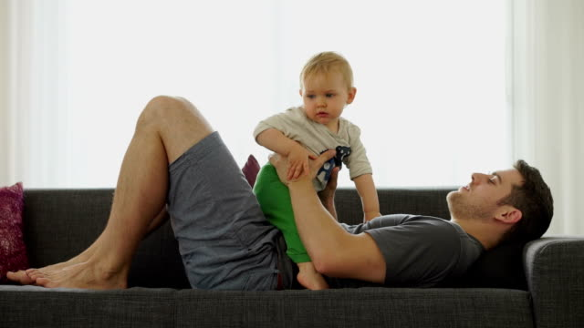 young dad with baby son on couch