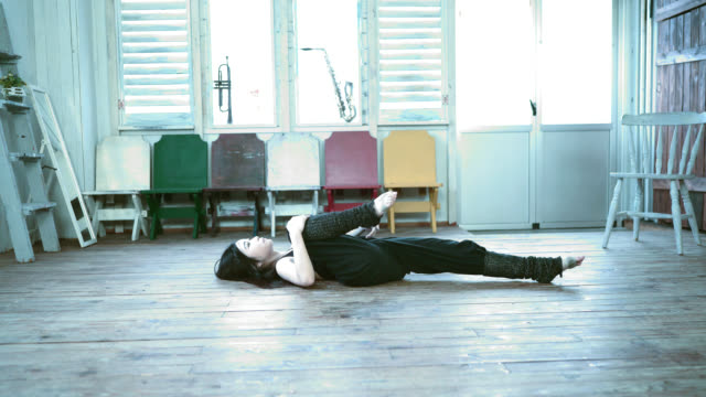 young dancer lie on wooden floor and stretching her legs - lypsekyo16 stock videos and b-roll footage