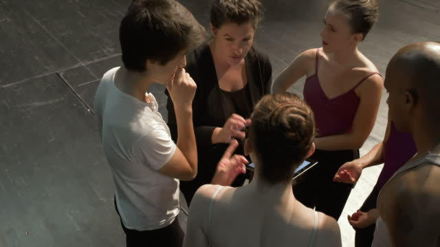 young dancers and woman in group on stage with digital tablet having a discussion. - auditorium stock videos and b-roll footage