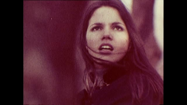 vídeos de stock e filmes b-roll de young, dark-haired 1960s girl in cape explores multiple landscapes - liverpool inglaterra