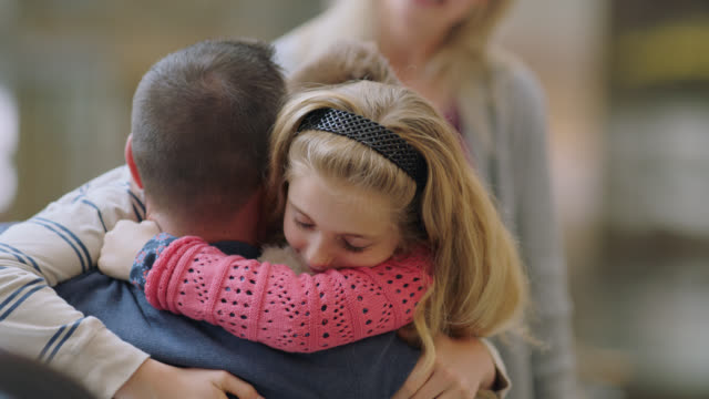 slo mo. young daughter embraces her father with mother in background. - arrival stock videos & royalty-free footage