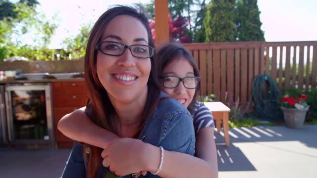 ms slo mo young daughter embracing smiling mother on backyard patio of home - brille stock-videos und b-roll-filmmaterial