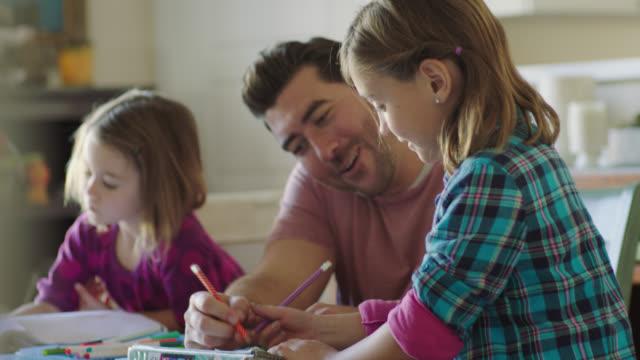 vídeos de stock e filmes b-roll de ms. young daughter gives dad a kiss as he helps girls with homework after school. - quadriculado