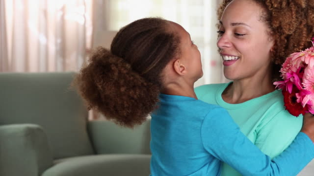 ms young daughter giving bouquet of flowers to mother, smiling at camera / richmond, virginia, united states - mother's day stock videos & royalty-free footage