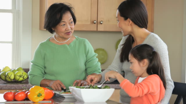 ms young daughter helping mother and grandparents prepare salad in kitchen / eastville, virginia, usa - salad stock videos & royalty-free footage