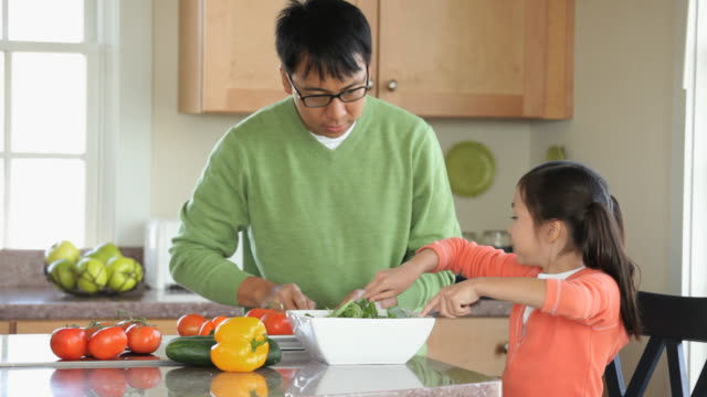ms pan young daughter helping parents prepare salad in kitchen / eastville, virginia, usa - eastville stock videos and b-roll footage