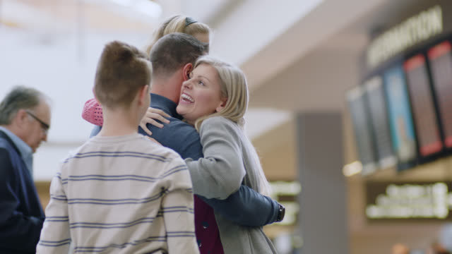vídeos y material grabado en eventos de stock de slo mo. young daughter, son and mother greet and hug father upon arrival at airport. - arrival
