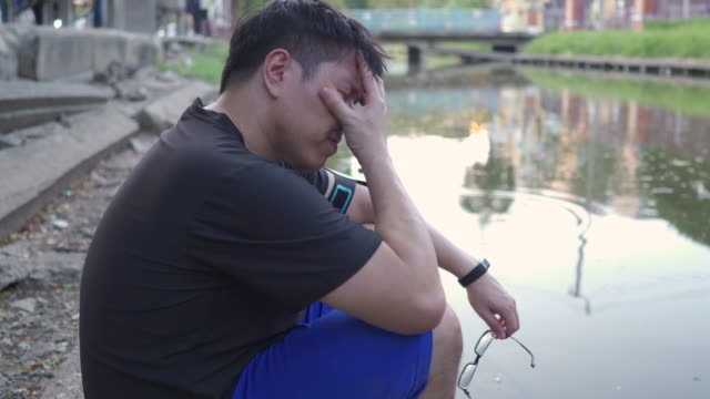 young depressed asian man sitting on near the pond depression, sadness, hardship, mental health concepts. - blame stock videos & royalty-free footage