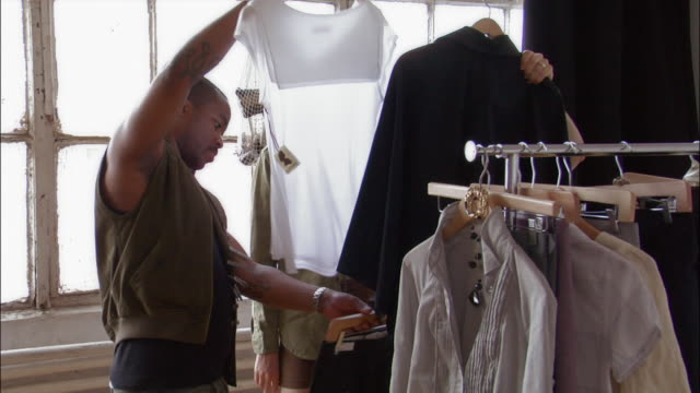 young design team looking through clothing rack / selecting outfits from rack - ファッションデザイナー点の映像素材/bロール