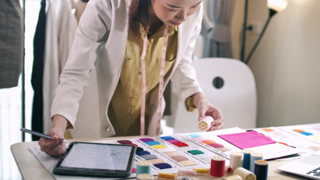 young designer measuring and matching materials for new collection in fashion design studio - designer clothing stock videos & royalty-free footage