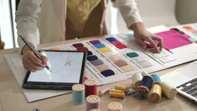young designer measuring and matching materials for new collection in fashion design studio using digital tablet - design studio stock videos & royalty-free footage