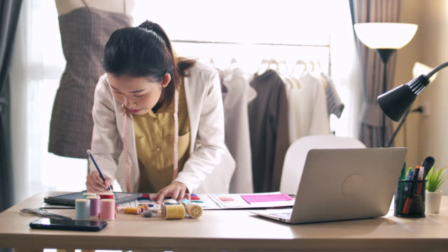 young designer measuring and matching materials for new collection in fashion design studio using digital tablet - designer clothing stock videos & royalty-free footage