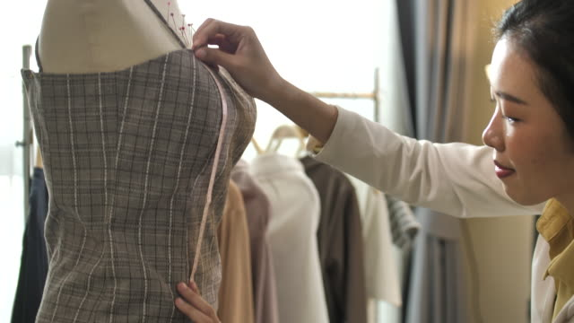 young designer measuring on her design clothing in fashion design studio - designer clothing stock videos & royalty-free footage