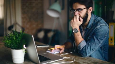 junge designer auf videokonferenz in seinem büro zu hause - one person stock-videos und b-roll-filmmaterial