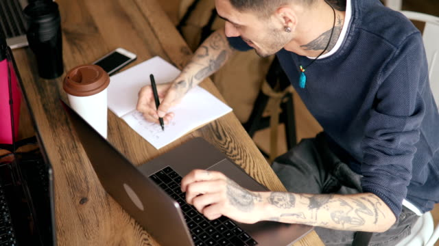 young designer working at small co-working office - tattoo stock videos & royalty-free footage