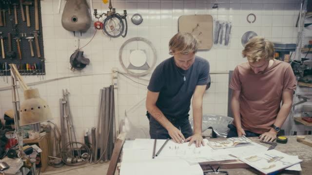 vidéos et rushes de jeunes concepteurs planifiant un produit dans l'atelier - gribouillage