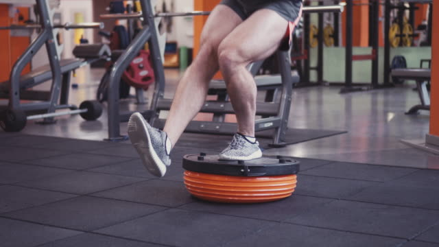 Young determined man doing squats on fitness ball