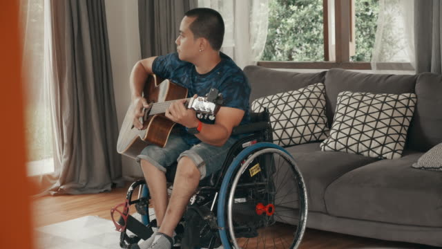 young disabled man playing guitar - persons with disabilities stock videos & royalty-free footage