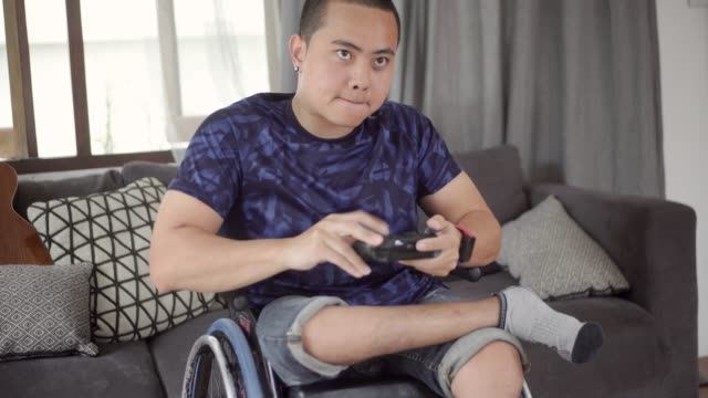 young disabled man playing video game. - polio stock videos & royalty-free footage