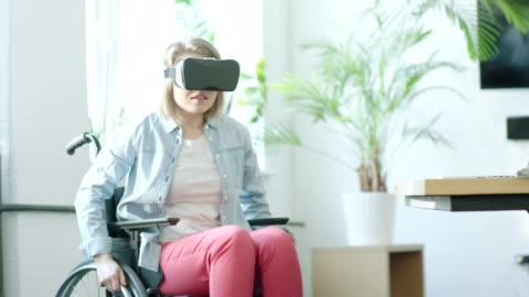 vídeos y material grabado en eventos de stock de jóvenes con discapacidad a mujer con casco de realidad virtual - simulador de realidad virtual