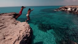 Young divers couple jumping off cliff into the ocean