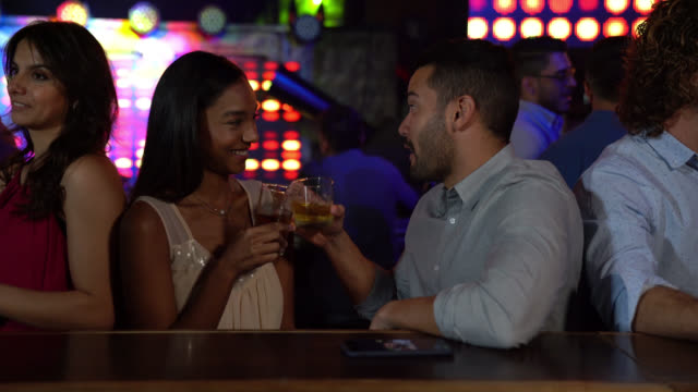 young diverse couple enjoying whiskey while talking and smiling at a bar - romance stock videos & royalty-free footage