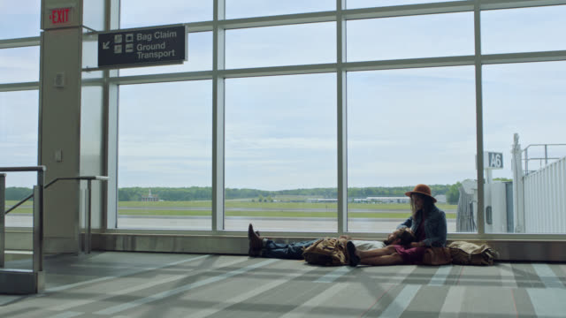 young diverse couple lounges while waiting in airpost terminal near window. - westernisation stock videos & royalty-free footage