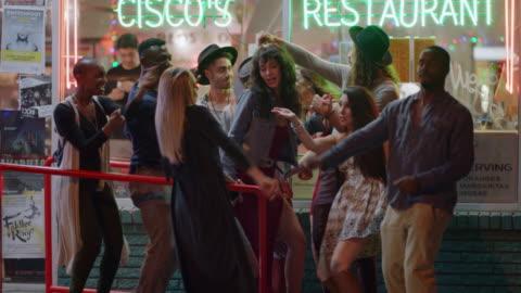 vídeos y material grabado en eventos de stock de young diverse group of friends dance and sing outside of a downtown restaurant in austin, texas. - amigos