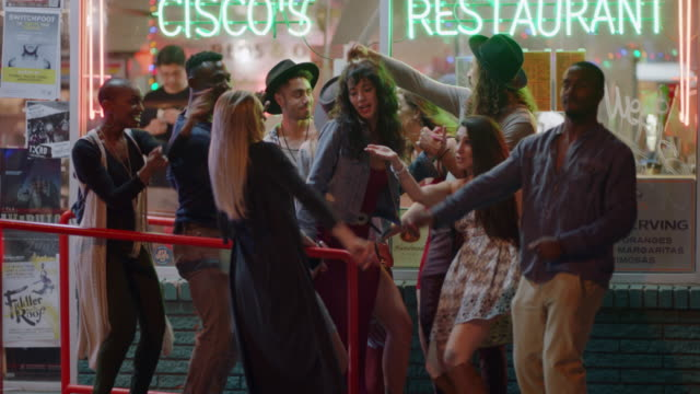 vídeos de stock e filmes b-roll de young diverse group of friends dance and sing outside of a downtown restaurant in austin, texas. - dance music